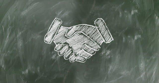 面接で企業人と熱い握手を交わしているイメージ図