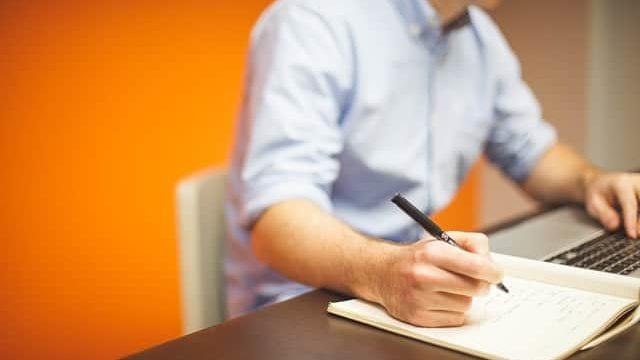 企業人から学んだことをノートに書いている理系学生